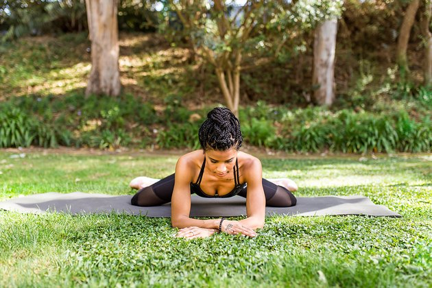 woman doing frog stretch on a yoga mat outside