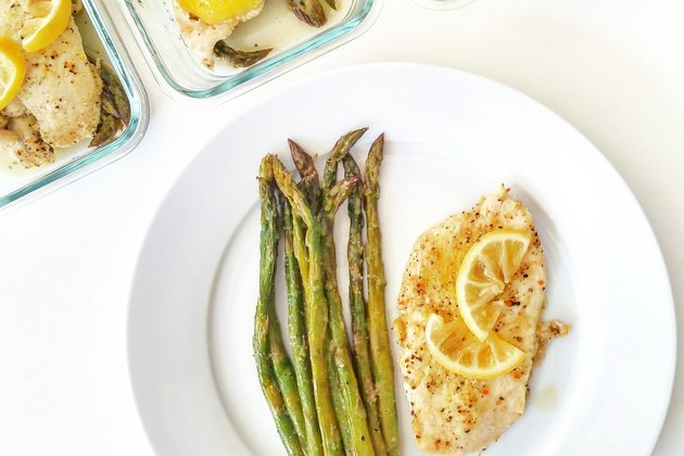 Top view of a plate with grilled chicken breast topped with lemon and a side of asparagus