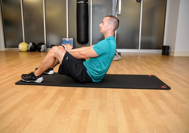 The top position of the kettlebell sit-up. The model is holding the kettlebell between his knees with his torso almost completely upright.