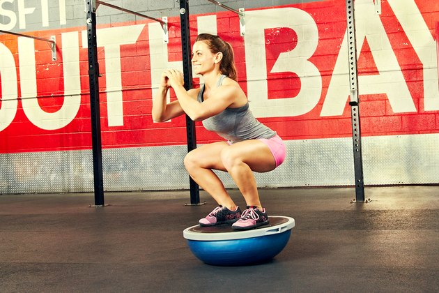 Woman performing BOSU ball exercise squat