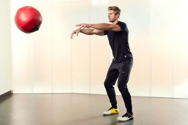 Man Demonstrating How to Do a Medicine Ball Chest Pass