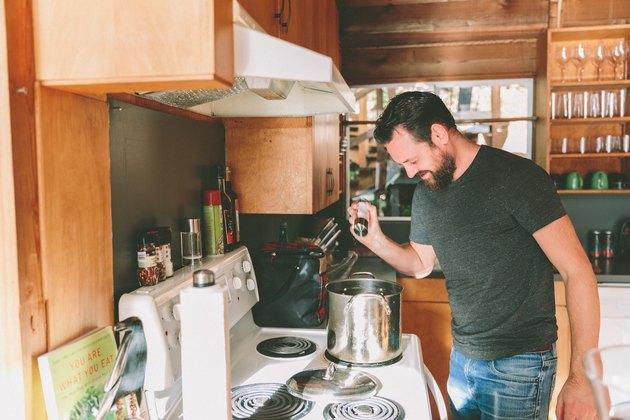 A man cooks.