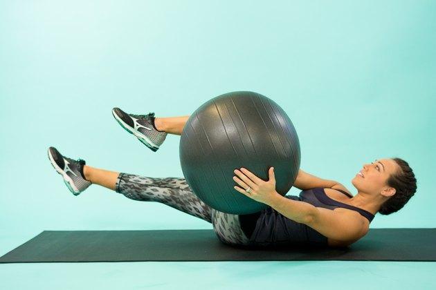 Woman performing Swiss ball cross crunch.