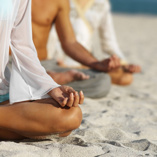 the physical postures of a group meditating at the beach