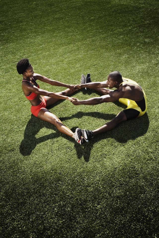 Athletic man and athletic woman stretching on field
