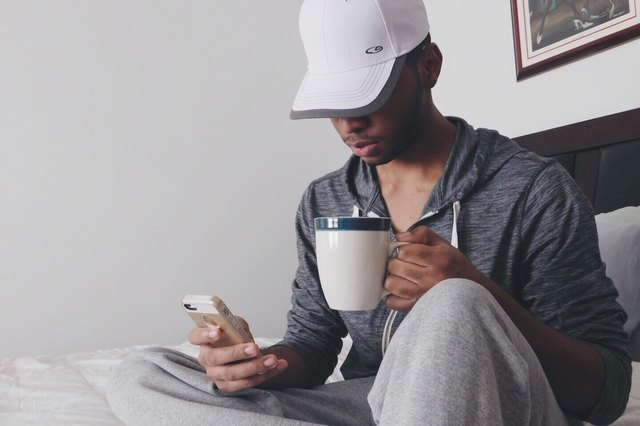 man checking his phone before bed