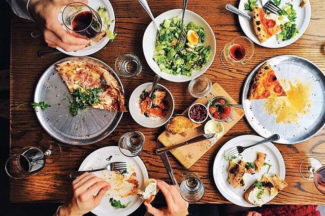 American foods like pizza and Cobb salad spread out on a table