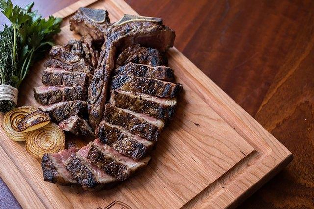 T bone steak on wood board