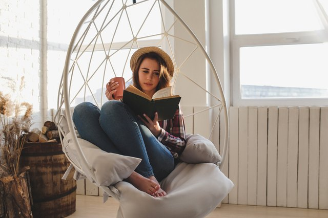woman sitting on chair reading book and sipping dandelion tea