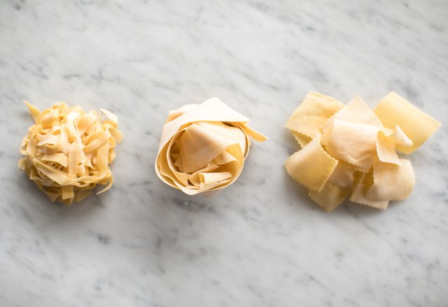 Different pasta shapes on marble background
