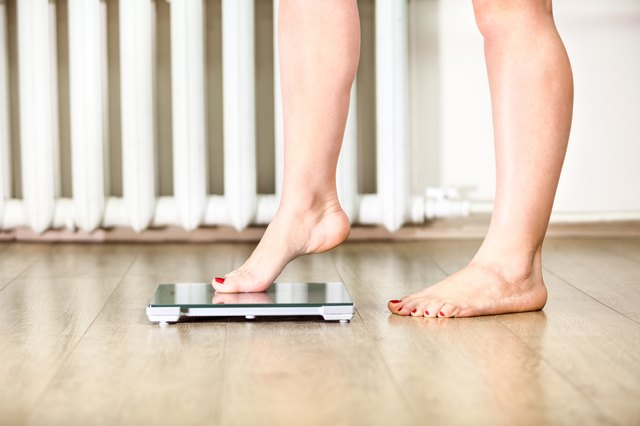 woman standing on bathroom scale to check her weight
