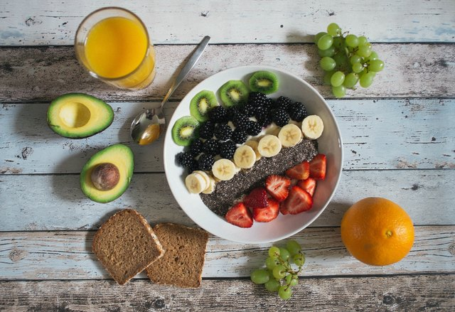 healthy smoothie bowl and fruit on a table for intermittent fasting