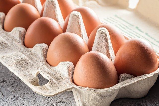 Farm raw fresh egg in pack on gray table scrambled eggs omelet fried egg
