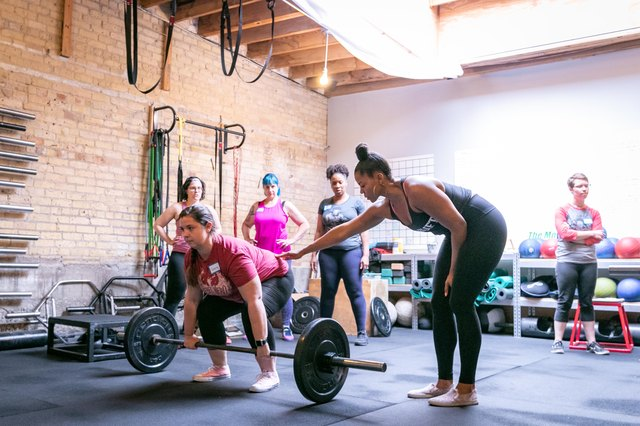 fitness professional and powerlifter Chrissy King helping a women with her deadlift form