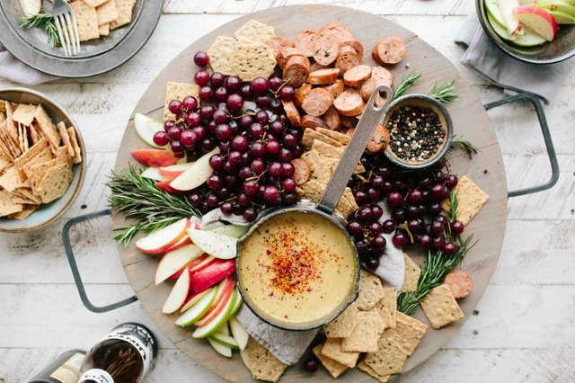 Cheese board filled with fruit, crackers and grapes