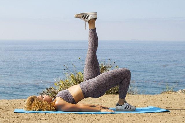 Daisha Graf doing a single-leg glute bridge on a yoga mat near the beach