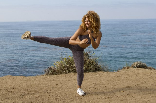 Daisha Graf doing squats with side kicks on the beach