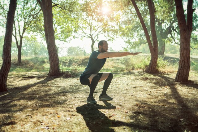 Athletic man doing squats on a forest
