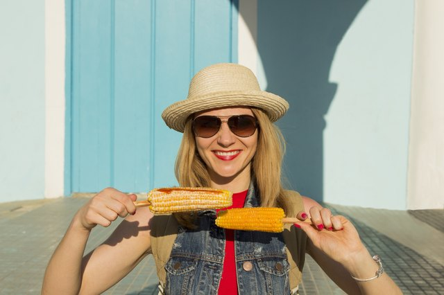 Woman in straw hat and sunglasses holds two corn cobs