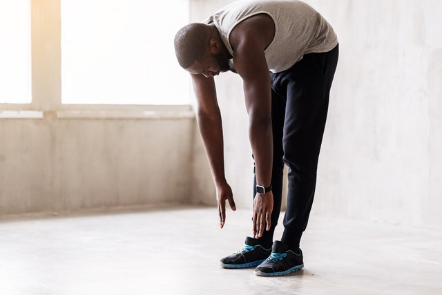 Calm african muscular guy doing warming-up exercises