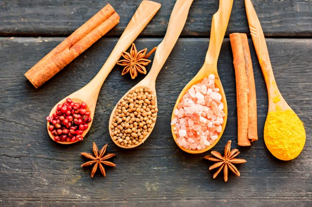 Various colorful herbs and spices in wooden spoons