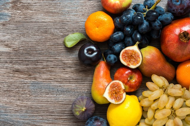 Juicy fresh fruit on a wooden dark table, top view.