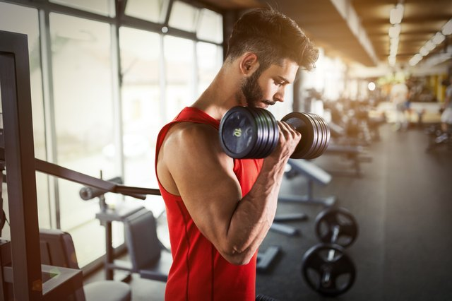 Determined male working out in gym lifting weights