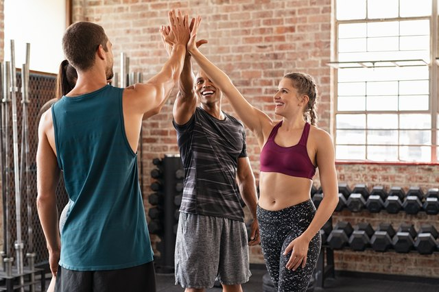 Happy team giving high five in gym