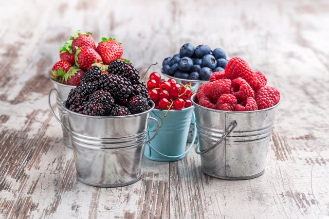 Colorful berries assortment in tin cans on rustic wooden table