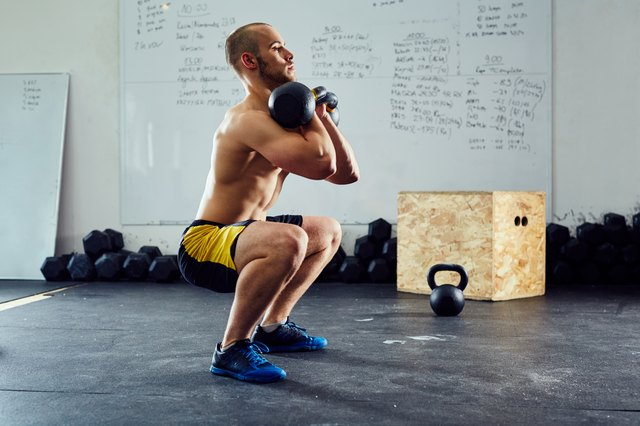 Young athletic man doing squats with kettlebells at the gym