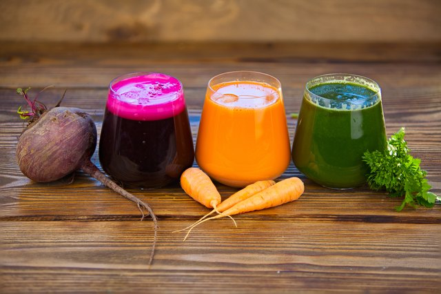three vegetable juice in glass cup on wooden background