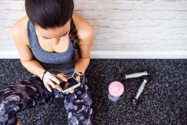 Fit woman in gym holding smartphone, brick wall