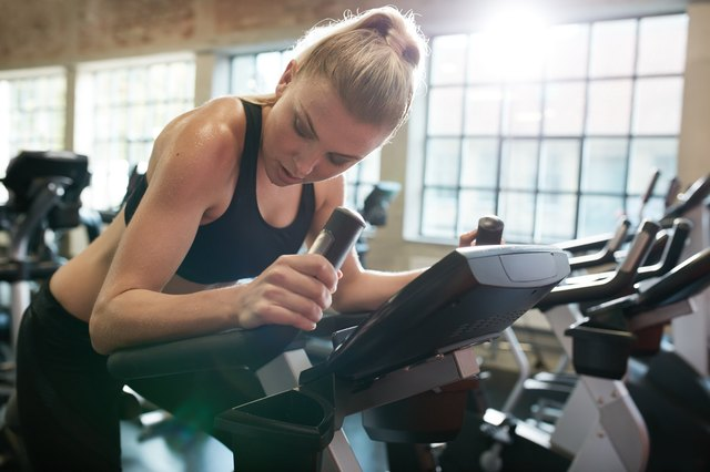Fit young female exercising on gym bike