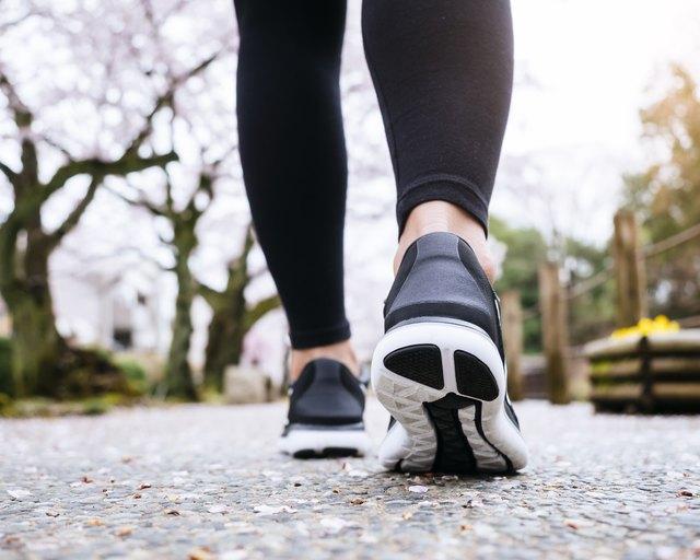 Woman Legs Sport shoe walk in Park outdoor Sakura tree