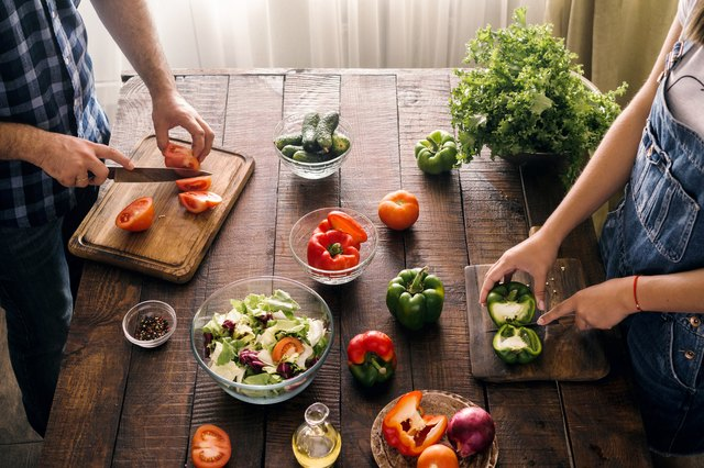 Married couple cooking together dinner vegetables salad in home kitchen, top view