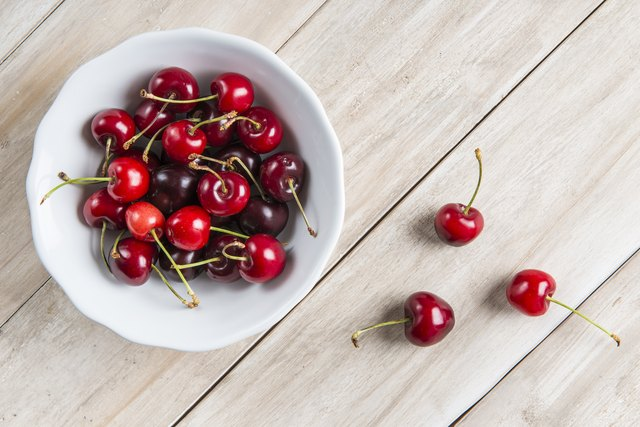 White bowl of cherries on the table