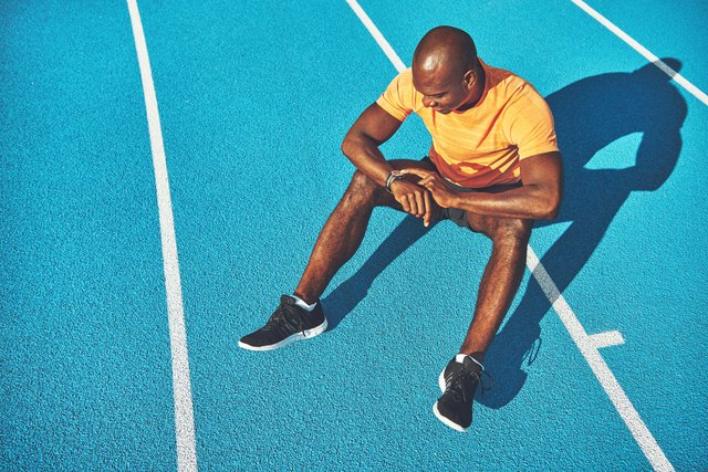 Young athlete sitting on a track checking his running time
