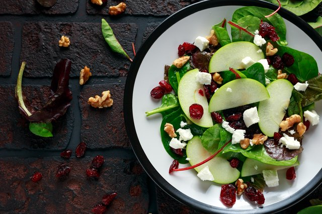 Homemade Autumn Apple Cranberry Salad with walnut, feta cheese and vegetables