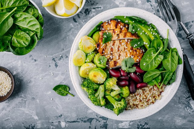 Healthy buddha bowl lunch with grilled chicken, quinoa, spinach, avocado, brussels sprouts, broccoli, red beans with sesame seeds