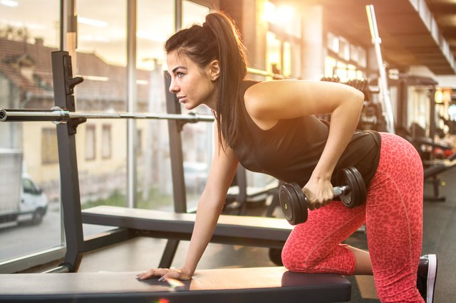 Young sexy woman doing exercises with dumbbell in gym.