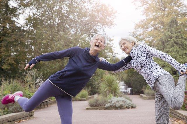 Senior women stretching legs in park.