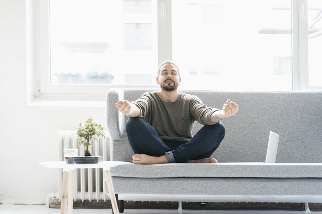 Portrait of man with eyes closed sitting on the couch doing yoga exercise