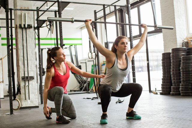 Personal trainer guiding woman doing barbell squats at gym