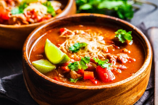 Traditional mexican bean soup with meat and cheese in wooden bowl, dark background
