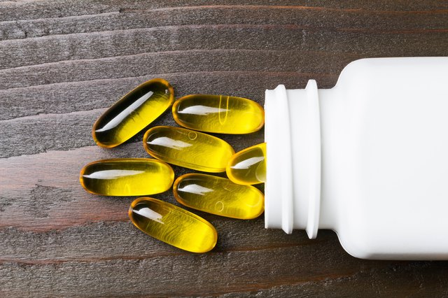 Yellow capsules omega 3, fatty acid, fish oil with white bottle on dark wooden table, macro image, top view