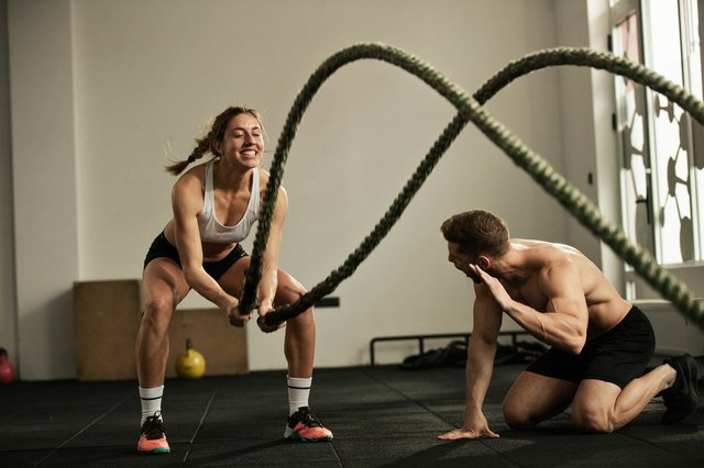 Athletic woman doing battle rope exercise with personal trainer in a gym.