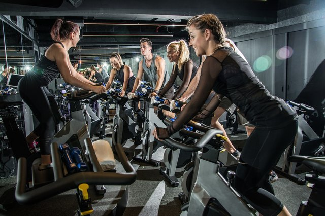 Group of sporty people with their instructor training on cycling class in gym