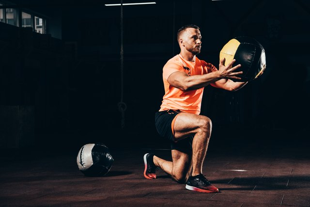 handsome athletic sportsman performing lunge with medicine ball in dark gym