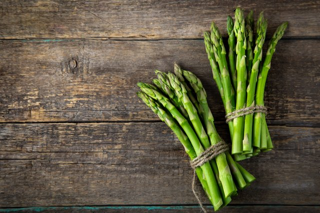 wooden bacckground with bunches of fresh green asparagus