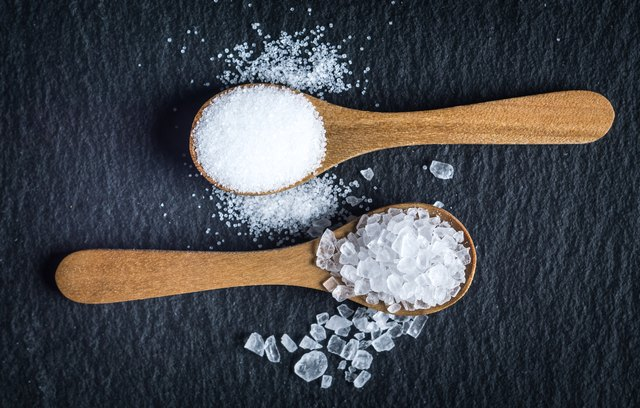 Different types of salt. Top view on two wooden spoons
